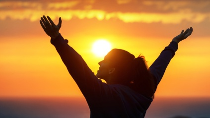 Free-woman-raising-arms-to-golden-sunset-summer-sky-like-praising